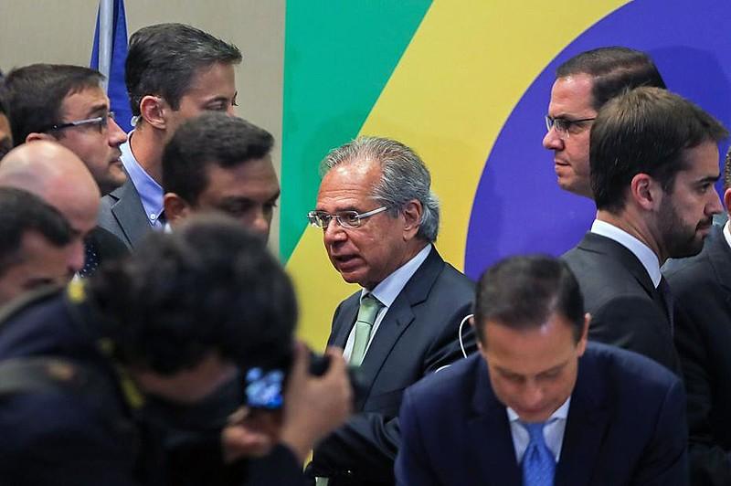 Ministro da Economia de Bolsonaro, Paulo Guedes [centro] aposta em modelo que deu errado