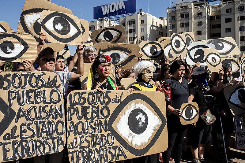 Chilenos exibem cartazes em referência aos projéteis que atingem os olhos dos manifestantes durante um protesto em dezembro