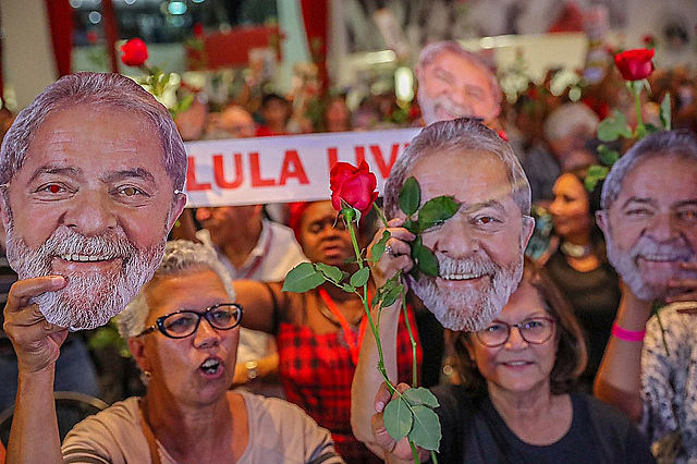 Supporters hold up masks of former president Lula during rally that called for his release from prison