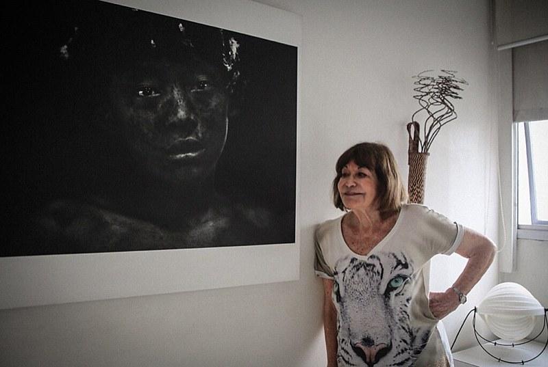 Fotógrafa Claudia Andujar posa em frente a uma de suas fotografias, em sua casa, em São Paulo