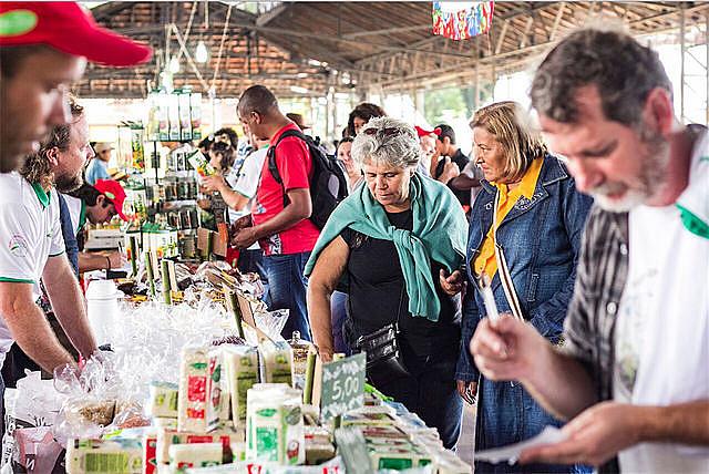 Consumidores de la Feria Nacional de Reforma Agraria examinan arroz orgánico de cooperativas de Rio Grande do Sul
