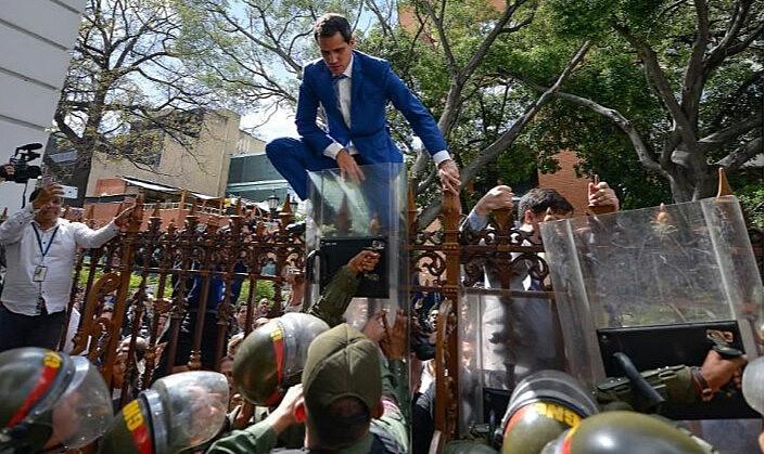 Juan Guaidó, ex-presidente da Assembléia Nacional da Venezuela, sobe uma cerca em uma tentativa fracassada de entrar na Casa