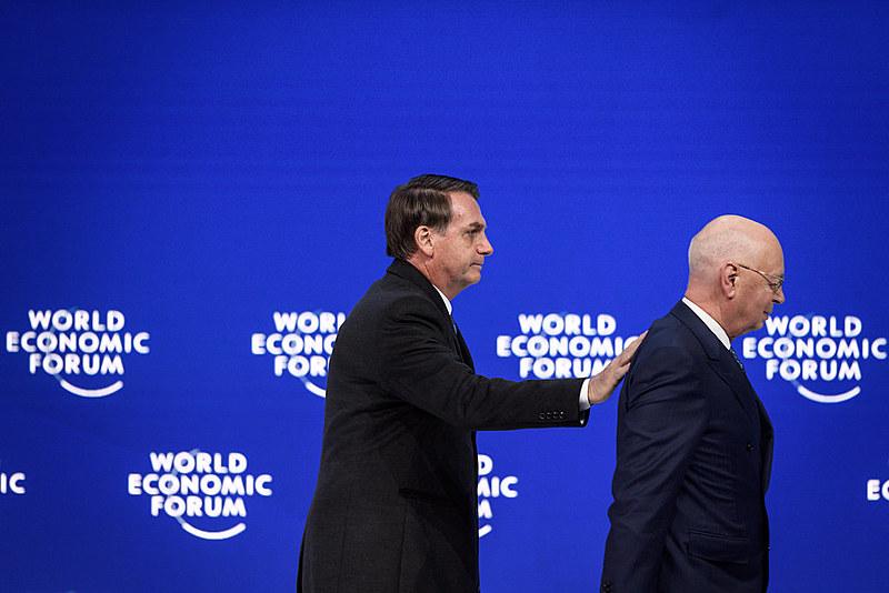 Bolsonaro deixa o palco acompanhado do presidente do Fórum Econômico Mundial, Klaus Schwab