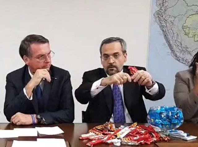Jair Bolsonaro (left) and Education minister Abraham Weintraub trying to explain education budget cuts using chocolate bars