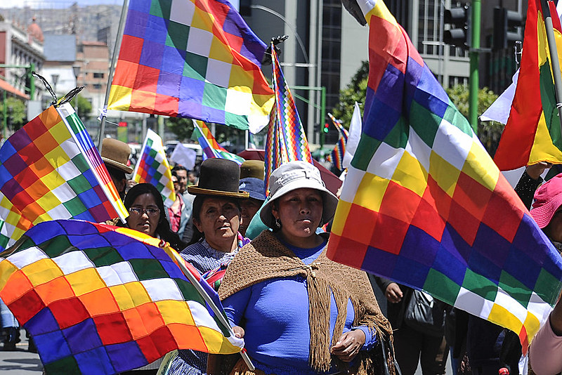 Manifestantes marcham na capital de Bolívia, La Paz, carregando bandeiras wiphala, símbolo dos povos originários