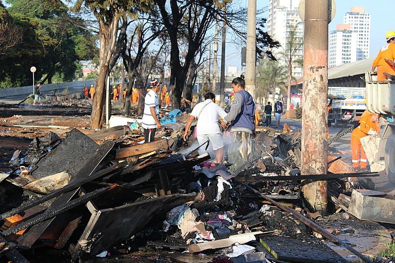 Moradoras buscam pertences nos escombros do incêndio, ocorrido na noite do último sábado (23)
