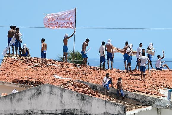 Alcaçuz: confronto entre tropas de choque da Polícia Militar e detentos; operários constroem muro de contâineres
