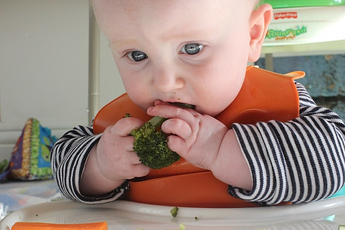Criança comendo brócolis