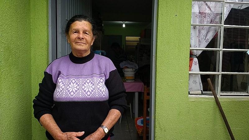 Enoemim posa em frente à casa em que mora hoje, mas não se esquece do antigo lar