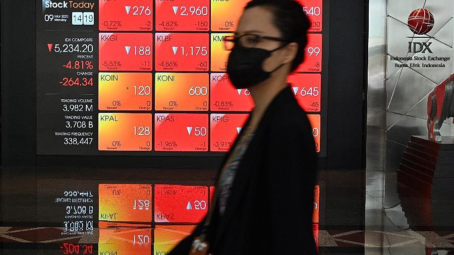 Mulher usa máscara na Bolsa de Valores da Indonésia, em Jacarta, no dia de caos nos mercados mundiais
