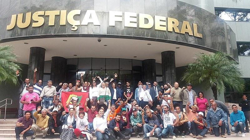 Comunidade posa em frente à 11ª Vara Federal de Curitiba, após audiência de conciliação.