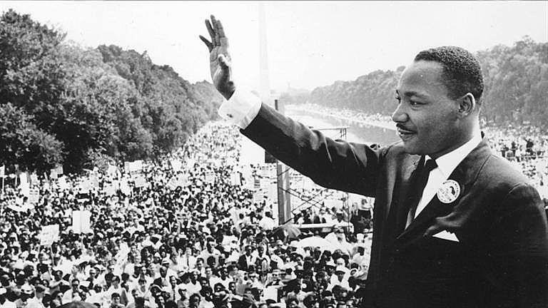 O reverendo Martin Luther King acena ao público presente na Marcha em Washington por direitos civis para negros e negras