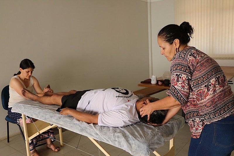Massoterapeuta e reikiana durante atendimento a militante nas atividades da greve de fome