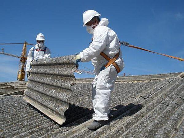 Homens manipulam telha de amianto