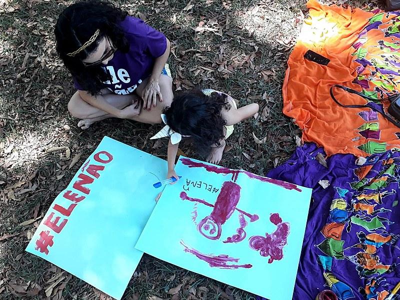 Servidora pública Clara Fagundes com a filha Helena, de 4 anos, durante oficina de cartazes em Brasília