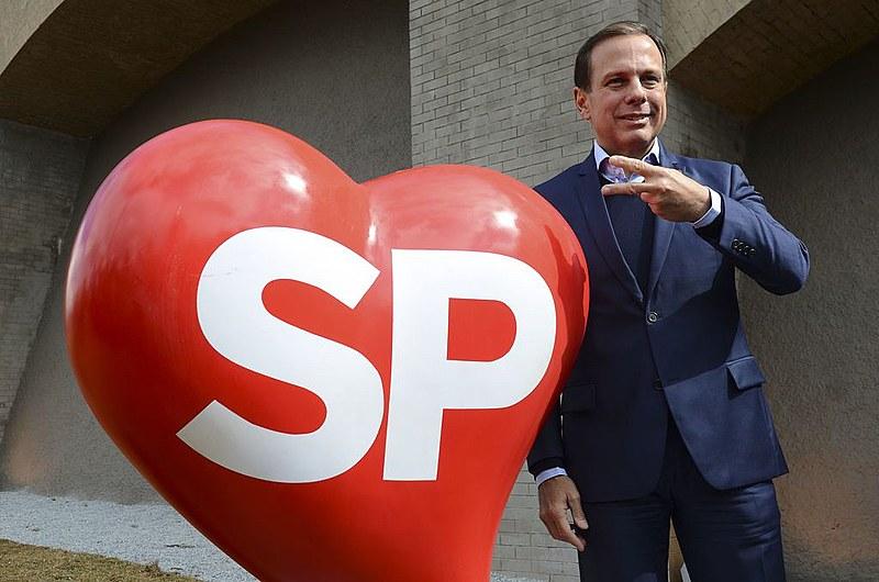 João Doria posa ao lado do símbolo do programa SP Cidade Linda; Justiça condenou o ex-prefeito por publicidade irregular