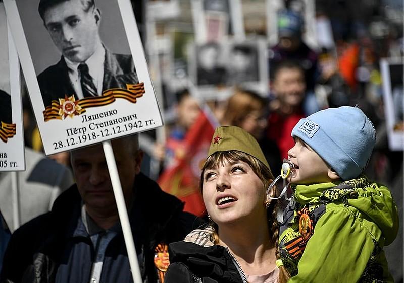 Mulher segura cartaz que traz foto de um herói de guerra na Praça Vermelha, em Moscou