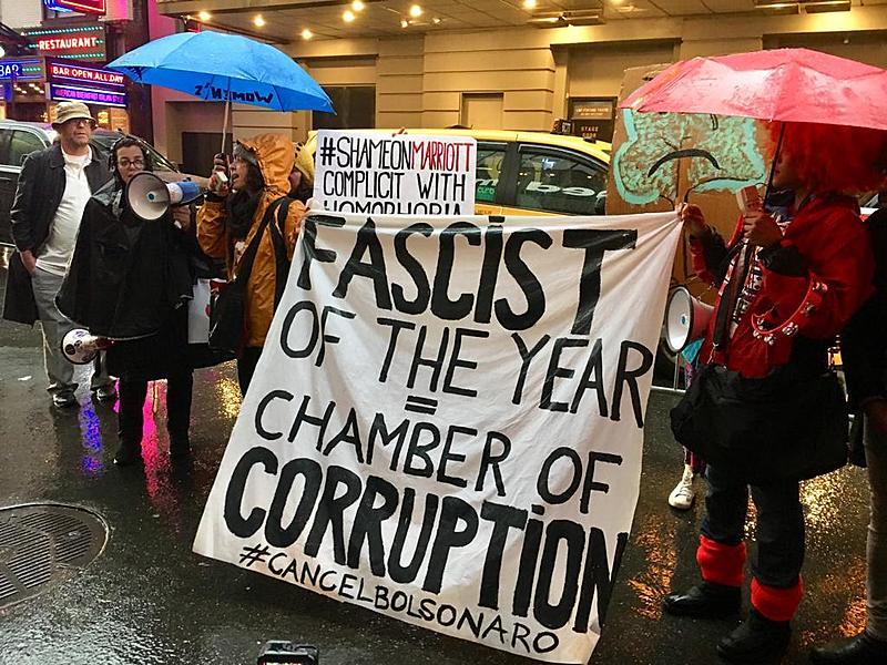 """Manifestante com faixa com os dizeres """"Fascista do Ano"""" e """"Câmera da Corrupção"""" em ato em Nova York"""