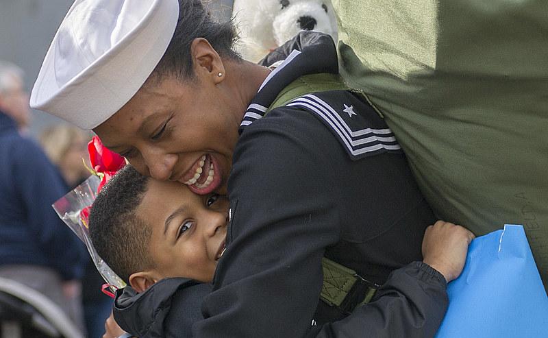 Marinheira abraça o filho durante a festa do regresso do seu navio