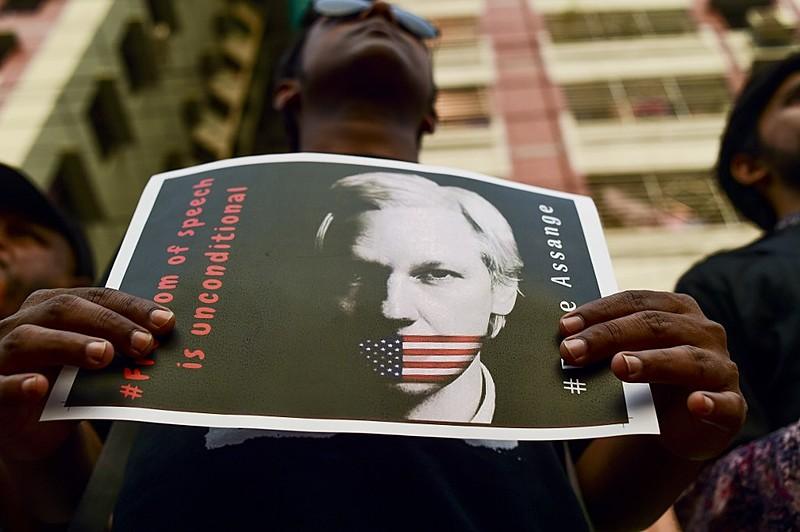 Manifestante segura foto de Assange amordaçado pela bandeira dos EUA em ato realizado em Bangladesh em abril de 2019