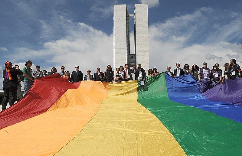 Ativistas LGBTs seguram bandeira arco íris na frente do Congresso Nacional durante a primeira Marcha Contra a Homofobia