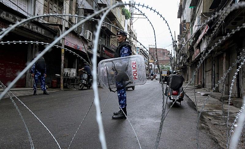 Soldado inidiano patrulha rua bloqueada na Caxemira