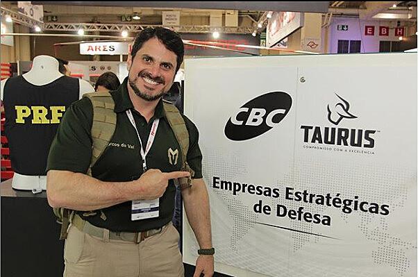 Senador, que trabalhava como instrutor, posa ao lado de banner em feira de armas realizada no Brasil
