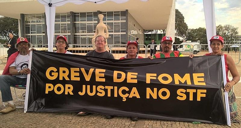 Militantes que estão em greve de fome desde a última terça (31) seguram faixa em frente à sede do STF em Brasília