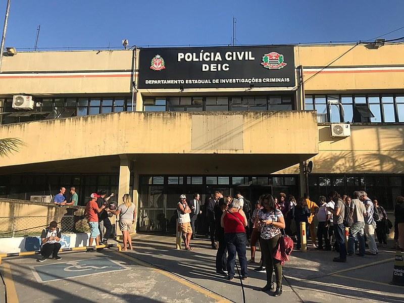 Integrantes de movimentos de moradia aguardam do lado de fora do DEIC