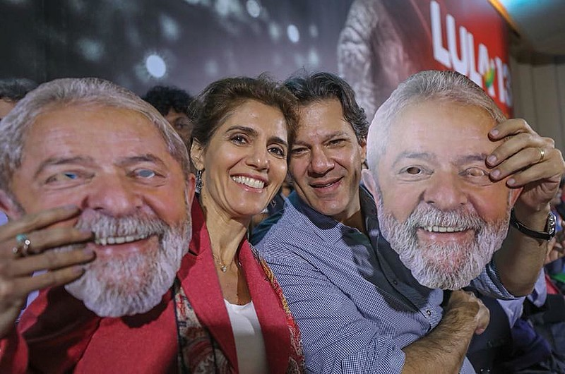 Ana Estela e Fernando Haddad seguram máscaras de Lula durante a campanha