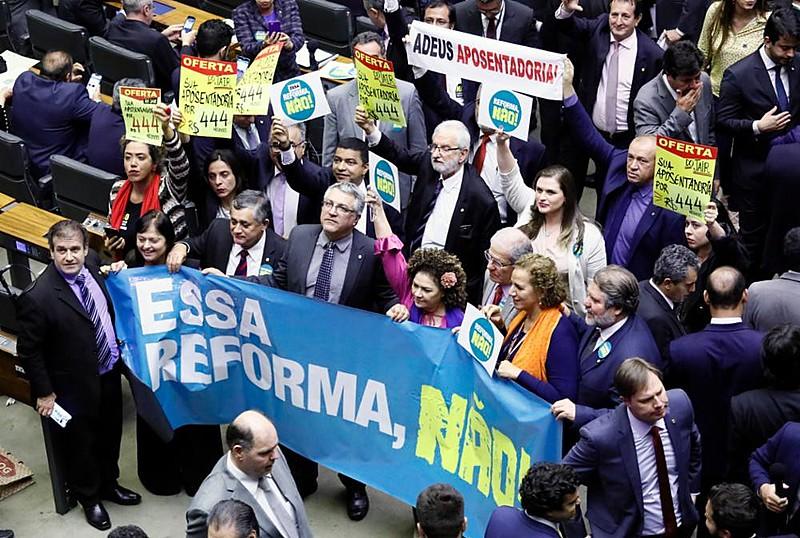 Deputados de oposição levaram cartazes contra a reforma durante a votação do projeto