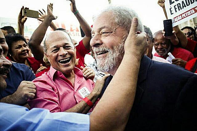 Former president Luiz Inácio Lula da Silva is greeted by supporters on the 1st caravan tour