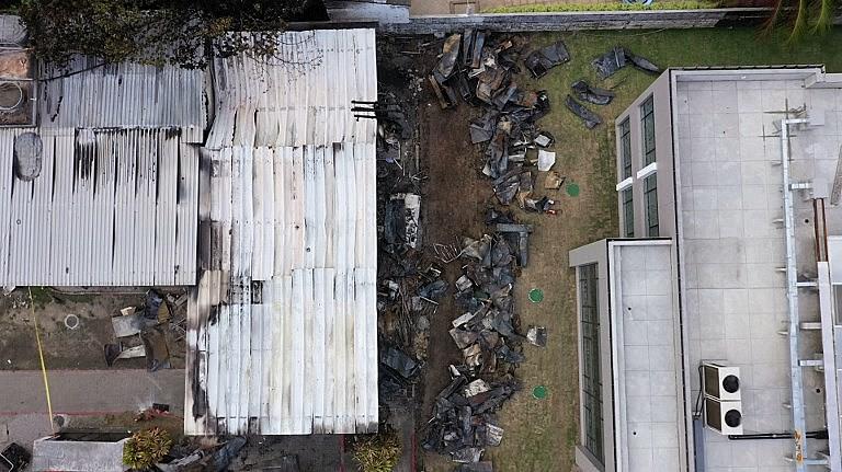 Vista área após incêndio nos contêineres onde meninos entre 14 e 17 anos dormiam; acidente deixou 10 mortos