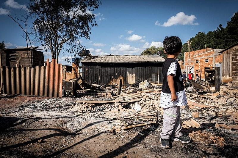 Garoto observa os escombros de ocupação incendiada
