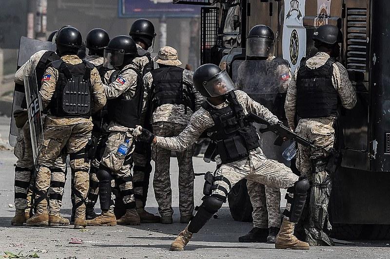Policial atira pedra em manifestantes próximos à sede da ONU em Porto Príncipe na sexta-feira (4)