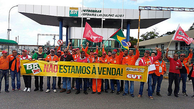 "Oil workers stand against privatization of state-owned oil giant Petrobras. The banner reads ""We're not for sale"""