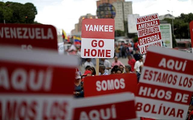 Apoiadores de Maduro seguram cartazes contra EUA