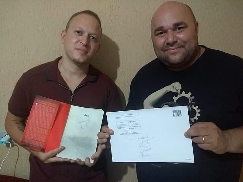 Antonio Elandio (dir.) posa com o  diploma ao lado do primo