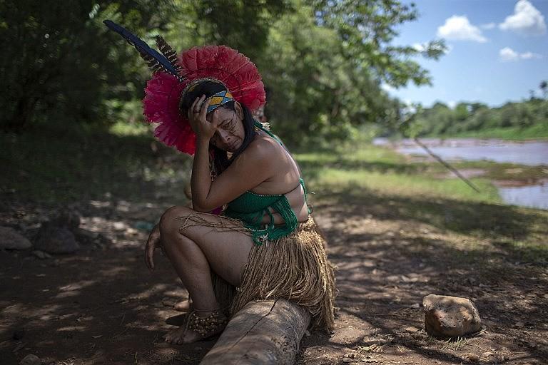 Indígena da comunidade Pataxo Ha-ha-hae chora ao lado do rio Paraopeba