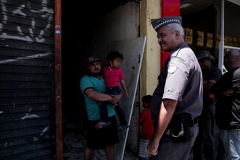 Policial sorri em frente ao cortiço onde moravam 40 famílias, na região da Luz. Imóvel foi desocupado sem auxílio de órgãos municipais