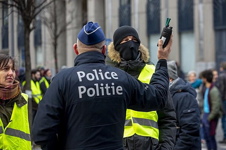 Policial belga conversa com manifestantes vestidos com coletes amarelos durante protesto no centro de Bruxelas no sábado