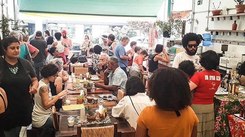 Dezenas de pessoas desfrutam de produtos da reforma agrária durante almoço no Armazém do Campo