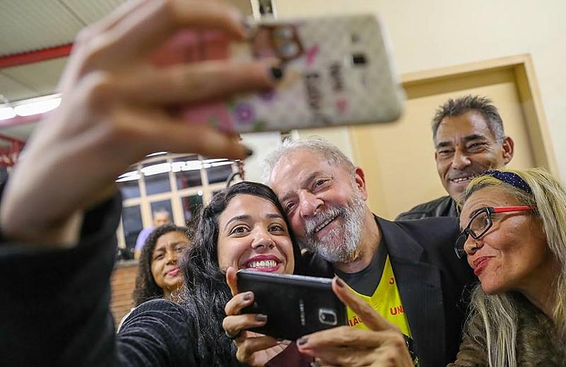 Lula foi ovacionado pelas pessoas presentes, tirou fotos e distribuiu autógrafos