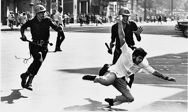 Um estudante de medicina cai na Cinelândia, no Rio de Janeiro, ao ser perseguido por policiais durante a ditadura militar.