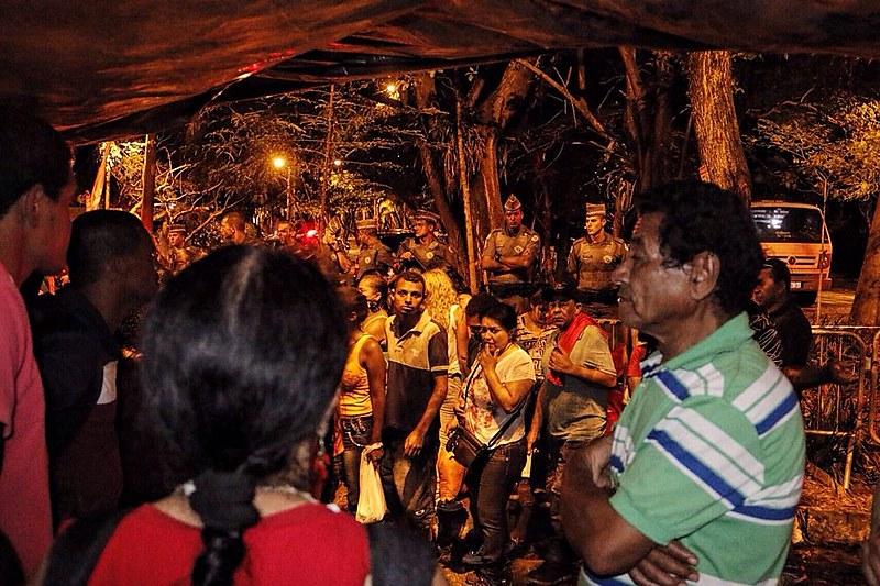 Ocupantes e a Polícia Militar ao fundo, que estava escoltando a casa desde a manhã deste domingo