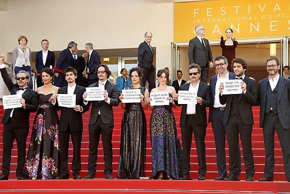 Equipe do filme Aquarius, dirigido pelo brasileiro Kleber Mendonça Filho, protestam no tapete vermelho do Festival de Cinema de Cannes