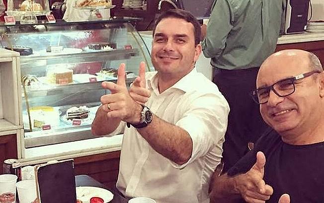 """Flávio Bolsonaro e Fabrício Queiroz fazem """"arminha com a mão"""" durante momento de descontração"""
