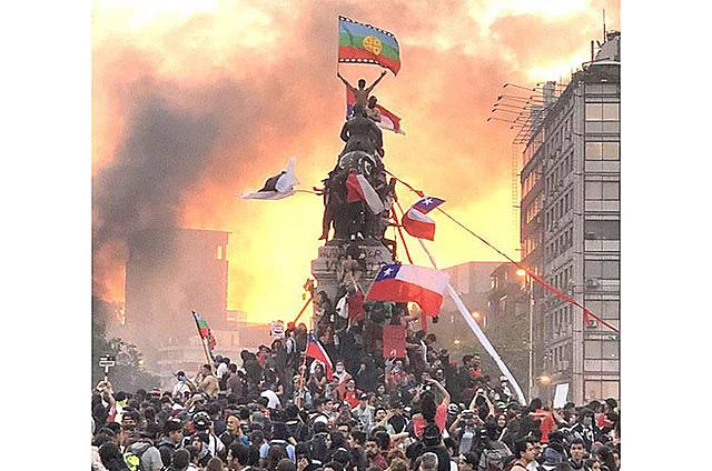 Manifestante com bandeira Mapuche no topo de estátua militar em Santiago (Chile), durante protesto do dia 25 de outubro