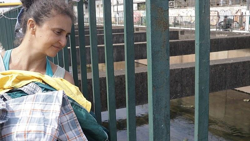 Ana Paula observa o Rio Tamanduateí depois de tirar as roupas secas pelo sol