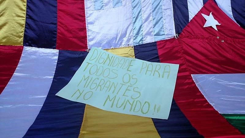 Cartaz na Marcha dos Imigrantes de 2016 pede dignidade para os migrantes no mundo todo